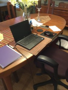A laptop on a dinning table.