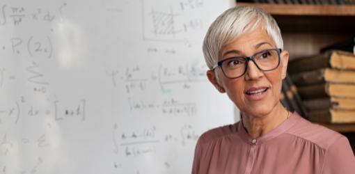 Portrait of professor explaining on whiteboard math formulas.