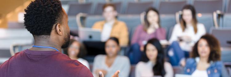 Un professeur d'université fait des gestes pendant un cours.